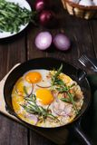 Uova fritte con bacon e pianta fotografia stock