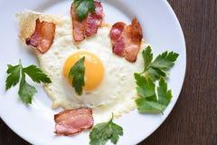 Uova fritte con bacon e prezzemolo leggermente fritti su un piatto bianco immagini stock libere da diritti