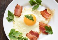 Uova fritte con bacon e prezzemolo leggermente fritti su un piatto bianco immagine stock