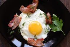 Uova fritte con bacon e prezzemolo leggermente fritti su un piatto posteriore fotografia stock