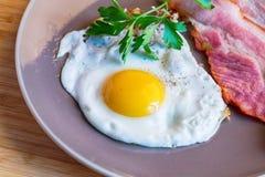 Uova fritte con bacon e verdi su un piatto fotografia stock libera da diritti