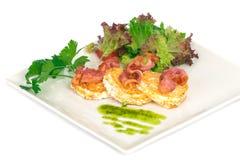 Uova fritte con bacon ed insalata verde sul piatto bianco Fotografie Stock