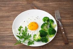 Uova fritte con i broccoli e verdi su una tavola di legno Fotografie Stock