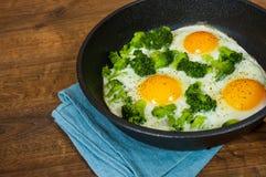 Uova fritte con i broccoli in una padella del ferro sui precedenti di legno marroni della tavola Fotografia Stock