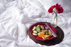 Uova fritte con i pani tostati ed il tè a letto Immagine Stock