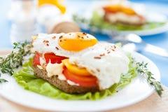 Uova fritte con i peperoni ed i pomodori su una zolla bianca Fotografie Stock Libere da Diritti