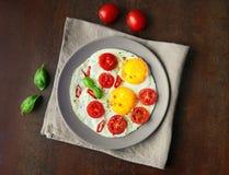 Uova fritte con i pomodori ciliegia ed il peperoncino, esperti con la s Fotografia Stock