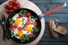 Uova fritte con i pomodori del bacon ed i verdi, pentola del ghisa, vista superiore fotografia stock