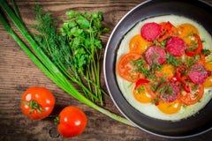 Uova fritte con i verdi, la salsiccia ed il pomodoro fotografia stock libera da diritti