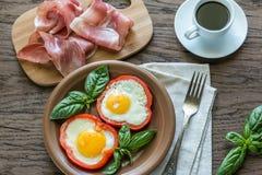 Uova fritte con il prosciutto di Parma sulla tavola di legno Fotografie Stock