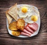 Uova fritte con il prosciutto ed i pezzi di pane fotografie stock