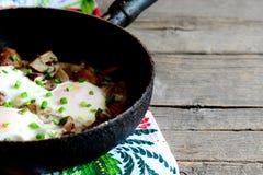 Uova fritte con la ricetta dei funghi Uova fritte con i funghi in una pentola su fondo di legno d'annata con lo spazio della copi Fotografia Stock
