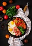 Uova fritte con la salsiccia e le verdure in una padella Fotografie Stock