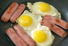 Uova fritte con le salsiccie, 3 uova fritte, parecchie salsiccie su un bl Fotografie Stock