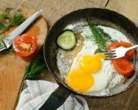 Uova fritte con le verdure in una padella fotografia stock