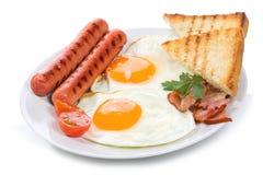 Uova fritte con pancetta affumicata, le salsiccie ed i pani tostati Fotografia Stock