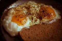 Uova fritte con pane in una padella e spruzzato con condimento Fotografie Stock