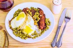 Uova fritte delle uova fritte con la salsiccia ed i piselli Fotografia Stock