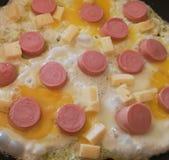 Uova fritte di cottura domestica con le salsiccie ed il formaggio immagine stock libera da diritti