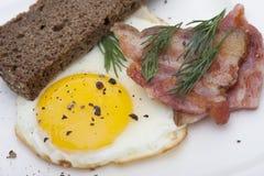 Uova fritte e bacon per la prima colazione isolata su fondo bianco fotografia stock