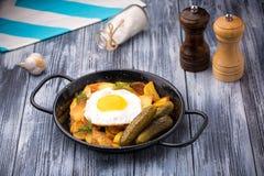 Uova fritte e patate in una padella con i sottaceti su fondo di legno Fotografie Stock