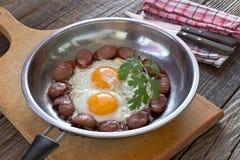 Uova fritte e salsiccie nella cottura della pentola sulla tavola di legno Fotografia Stock