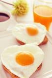 Uova fritte in forma di cuore, pane e succo d'arancia Fotografie Stock Libere da Diritti