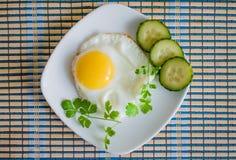 Uova fritte fritte con i cetrioli Fotografia Stock