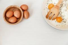 Uova fritte nella padella, ingredienti della prima colazione, accessori della cucina Uova di Brown fresche nel piatto di legno Co Immagine Stock Libera da Diritti