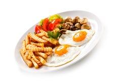 Uova fritte, patate fritte e verdure Immagini Stock
