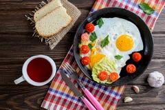 Uova fritte in pentola con il pomodoro, il pane, il pepe ed il prezzemolo fotografia stock