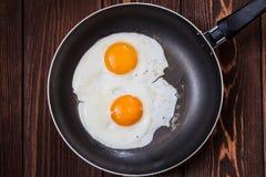 Uova fritte in pentola con la maniglia sulla tavola Fotografie Stock