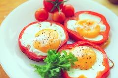 Uova fritte in peperoni Le uova fritte in paprica sono servito sul piatto bianco su fondo di legno Immagine tonificata Immagini Stock Libere da Diritti