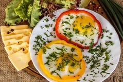 Uova fritte in peperoni variopinti su un bordo di legno anziano marrone Immagini Stock