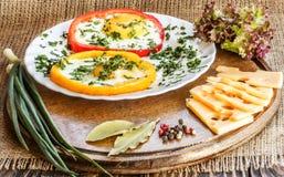 Uova fritte in peperoni variopinti su un bordo di legno anziano marrone Immagine Stock Libera da Diritti
