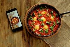 Uova fritte in salsa al pomodoro in una pentola del ghisa ed in uno smartphone Immagine Stock
