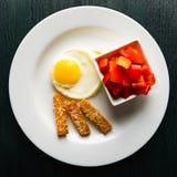Uova fritte su un piatto rotondo con i crostini del formaggio e del peperone dolce Fotografia Stock Libera da Diritti