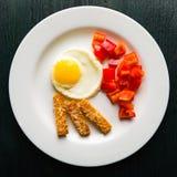 Uova fritte su un piatto rotondo con i crostini del formaggio e del peperone dolce Fotografia Stock