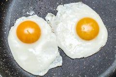 Uova fritte in una padella immagine stock