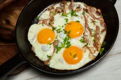 Uova fritte in una padella con becon Uova fritte con bacon in una pentola esperta con le erbe ed il pepe Fotografie Stock