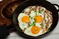 Uova fritte in una padella con becon Uova fritte con bacon in una pentola esperta con le erbe ed il pepe Immagine Stock Libera da Diritti