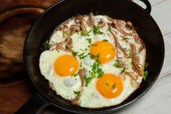 Uova fritte in una padella con becon Uova fritte con bacon in una pentola esperta con le erbe ed il pepe Immagine Stock