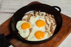 Uova fritte in una padella con becon Uova fritte con bacon in una pentola esperta con le erbe ed il pepe Fotografia Stock Libera da Diritti