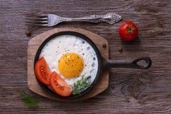 Uova fritte in una padella della ghisa con i pomodori ed il pepe nero immagini stock libere da diritti