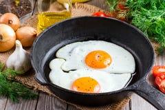 Uova fritte in una padella per la prima colazione su un fondo nero Immagine Stock