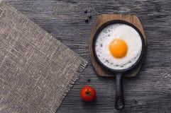 Uova fritte in una padella su una tavola di legno, vista superiore Spazio per testo Immagini Stock
