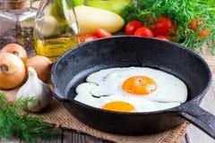 Uova fritte in una padella su un fondo nero Immagini Stock