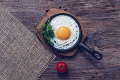 Uova fritte in una padella sulla tavola di legno, vista superiore Immagini Stock