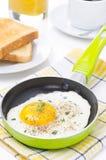 Uova fritte in una padella, in un pane tostato croccante, in un caffè ed in un succo d'arancia Immagini Stock Libere da Diritti
