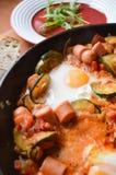 Uova fritte in una pentola con le verdure, primo piano Fotografie Stock